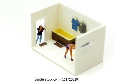 Miniature people : man is hiding behind  bathroom Spying. Voyeurism with woman  taking shower