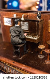 Miniature people man play mini piano dark wood artist art singer songwriter music musician old vintage house items sale garage storage container uk manchester london space for text advertisement