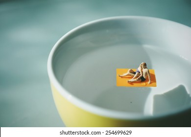 Miniature people man and woman on the  water cup of coffee