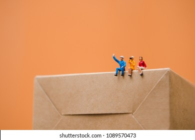 Miniature people, man and woman sitting on paper box using as business and social concept - Orange background