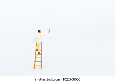Miniature people: mini figure with ladder and white painting  in front of a wall.