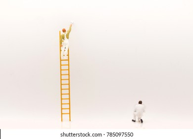 miniature people, mini figure with ladder and white paint in front of a wall and another one paint on bottom of wall.