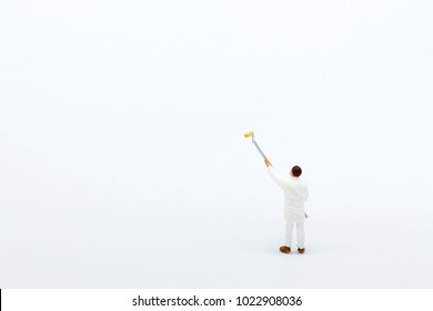 Miniature people: mini figure with long wood for painting  in front of a wall.