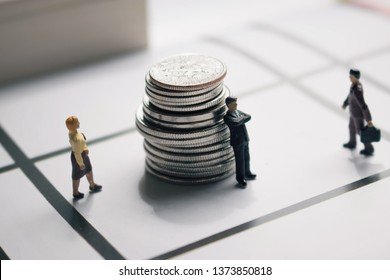Miniature people moving towards a stack of coins. Saving nickels and dimes. Wealth management or investment. Business or sales people compete for commission or earnings. Big money minimal background.