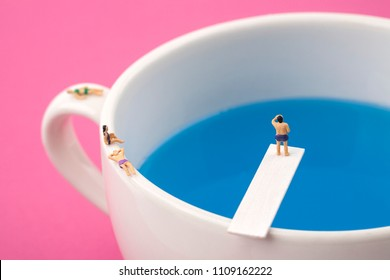 miniature people in mug cup swimming pool