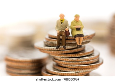 Miniature people, Old couple figure sitting on top of stack coins using as background retirement planning, Life insurance concept.