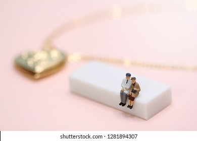 Miniature people old couple sitting on the white bench with golden heart locket on pink background with copy space, love and valentine's day concept