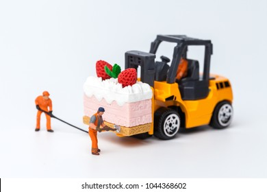 Miniature people on cake with strawberry on top, cooking and decoration concept. The concept of a collective solution to any problem. Close-up view.