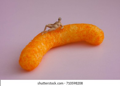 Miniature people on a cheese puff. Everyone enjoys a good snack. Tiny people on a huge orange cheesy. Absurd snack photo or food porn.