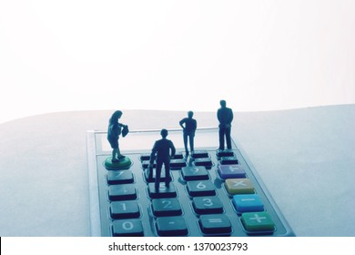 Miniature people on a desktop calculator. Certified accountants or financial planning team in a meeting.  Group of professional men and women crunching numbers under a deadline.Modern tax pros working