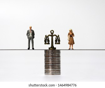 Miniature people on a pile of coins. Pile of coins and a miniature scale.