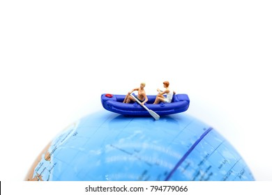 Miniature people : with paddle boat on mini world map , business and sport concept.