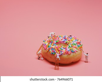 Miniature people painting color on donut.