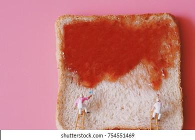Miniature people painting strawberry jam on bread.