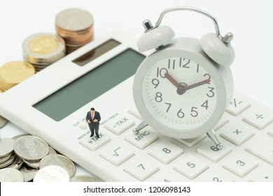 Miniature people Pay queue Annual income (TAX) for the year TAX Time watches put on the wood word TAX and white keyboard using as background business concept and finance concept with copy space