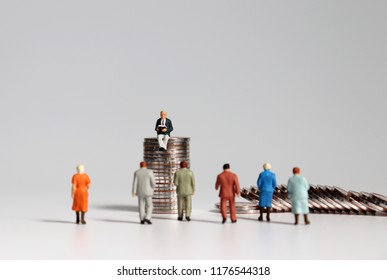 Miniature people and the pile of coins.