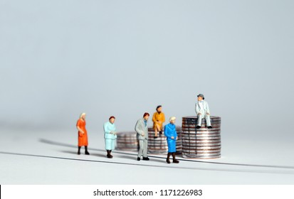 Miniature people and piles of coins. The concept of aging society and social costs.