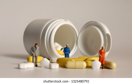 Miniature people and pills. The concept of the importance of disease management in the elderly.