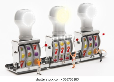 Miniature people playing slot machine.