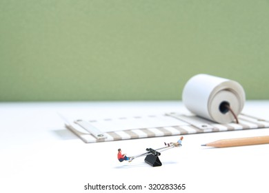 Miniature People playing with Stationary.