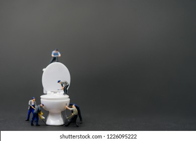 Miniature people :Plumber repairing toilet and change White Toilet Bowl and Flush Installation.Septic and Sanitary Residential Systems.Black background.