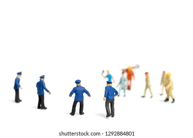 Miniature people : Police and an angry mob on white background