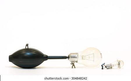 Miniature people pump up the light bulb