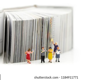 Miniature people : reading a book and Dictionary using for concept of Dictionary Day.