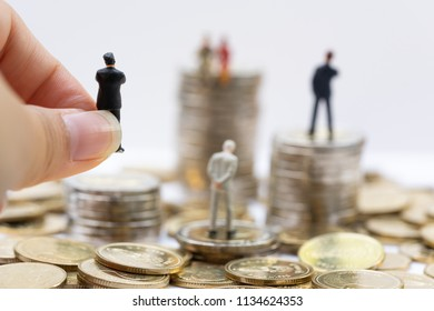 Miniature people: the recruiter sitting on top of coins stacks for finding the candidates below, recruitment process, HR, HRM, HRD concepts.