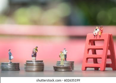 Miniature people: the recruiter sitting on top of red wooden ladder stack for finding the candidates on the coins stack, recruitment process, HR, HRM, HRD concepts.