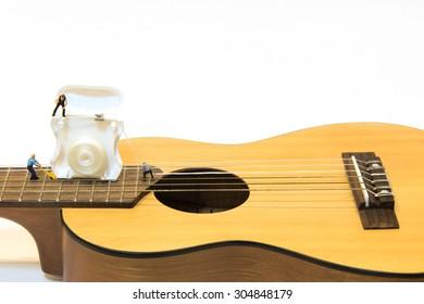 Miniature people repair guitar