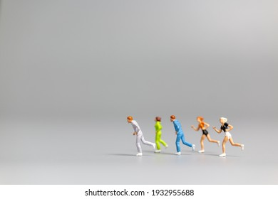 Miniature people Running on gray background and free space for text