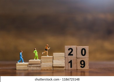 Miniature people  Running on wooden block number 2019 , Healthy lifestyle and sport concepts.