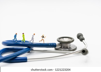 Miniature people running stethoscope. Health care and medical.