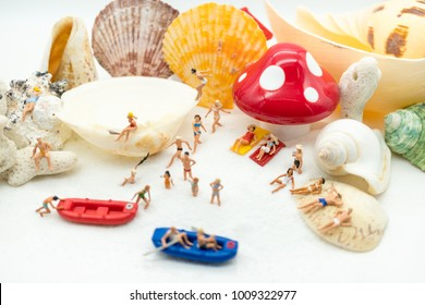 Miniature people: Sandy beach with tourists using as background traveling, exploring the world, business travel trip concept.