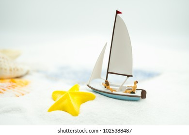 Miniature people: Sandy beach with tourists sail using as background traveling, exploring the world, business concept.