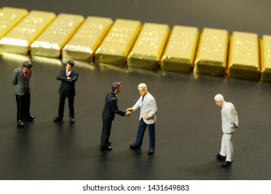 miniature people shaking hand with stack of gold bar on black background