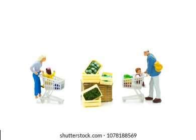 Miniature people: Shoppers with shopping cart to buy nature product for cook. Image use for marketing, business concept.