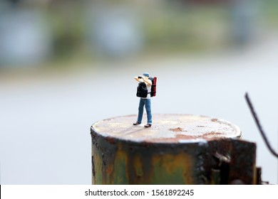 Miniature people : single backpacker trip isolated outdoor background