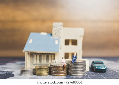 Miniature people sitting with coins money with home. Investment and growth in business concept.