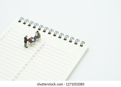 Miniature people sitting Consulting Advisory Services To pay taxes Business Operations on a Book Rankings (list). meeting or Discussion using as background business concept with copy space.