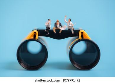 miniature people sitting on a binopolars