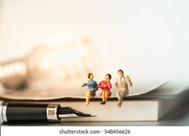 Miniature people sitting on book with lamp idea using as background education or business concept.