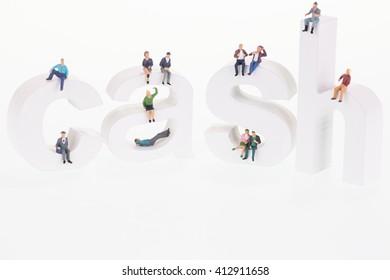 Miniature people sitting on cash letters