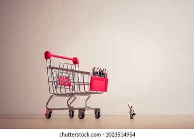 Miniature people sitting on a giant shopping cart. Saving and shopping concept.