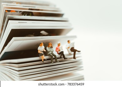 Miniature people sitting on paper using as education and social background concept - Vintage filter