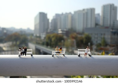 Miniature people sitting on park benches with a view on residential houses in Seoul, South Korea.
