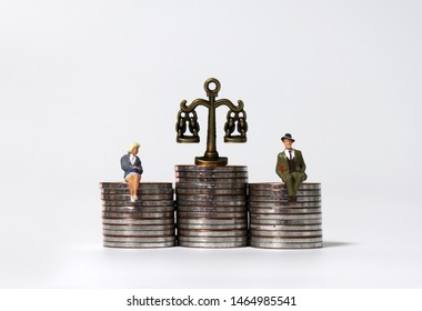 Miniature people sitting on pile of coins of the same height.