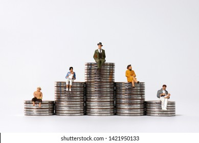 Miniature people sitting on piles of coins.