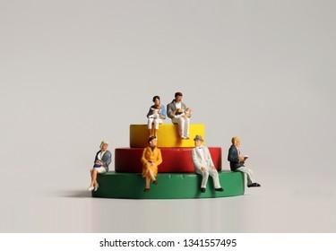 Miniature people sitting on wooden blocks.